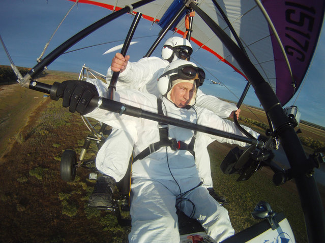 In this Wednesday Sept. 5, 2012,  file photo Russian President Vladimir Putin, foreground, flies in a motorized hang glider alongside a Siberian white crane, on the Yamal Peninsula, in Russia. (Photo by Alexei Druzhinin/AP Photo/RIA-Novosti/Presidential Press Service)