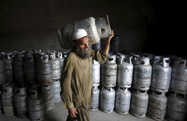 A worker carries a cylinder of Liquified Petroleum Gas (LPG) at a gas distribution centre in Peshawar, Pakistan April 29, 2015. (Photo by Fayaz Aziz/Reuters)