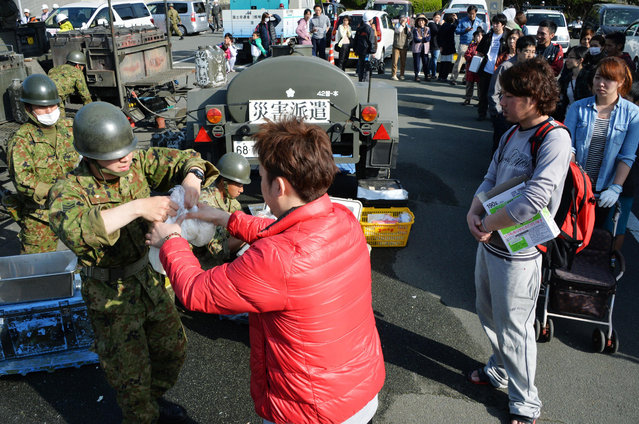 People line up to receive food at town office building in Mashiki, Kumamoto prefecture, southern Japan, Friday, April 15, 2016, a day after a strong earthquake struck. The quake toppled houses and buckled roads in southern Japan. (Photo by Shingo Nishizume/Kyodo News via AP Photo)