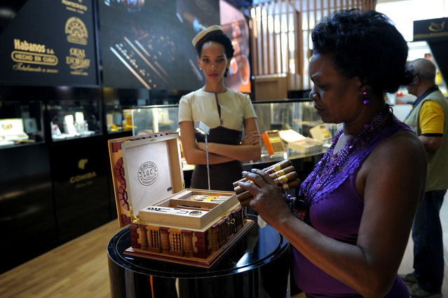 A visitor to the XIX Havana Cigar Festival looks at cigars at the Convention Palace in Havana on February 27, 2017. (Photo by Yamil Lage/AFP Photo)