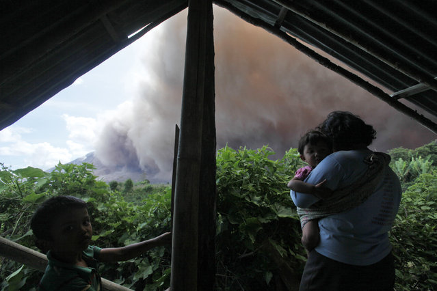 An Indonesian woman holds her daughter inside a hut as Mount Sinabung erupts in Tiga Kicat, North Sumatra, Indonesia, Saturday, June 13, 2015. The volcano, which was put on it highest alert level last week, has sporadically erupted since 2010 after being dormant for 400 years. (AP Photo/Binsar Bakkara)