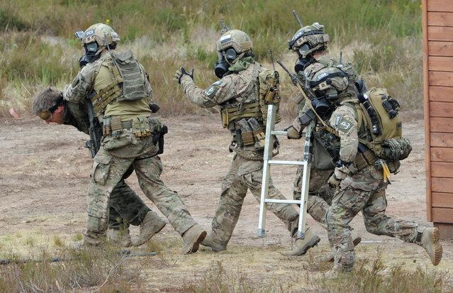 Soldiers lead a captive away during the NATO Noble Jump exercise on a training range near Swietoszow Zagan, Poland, Thursday, June 18, 2015. (AP Photo/Alik Keplicz)