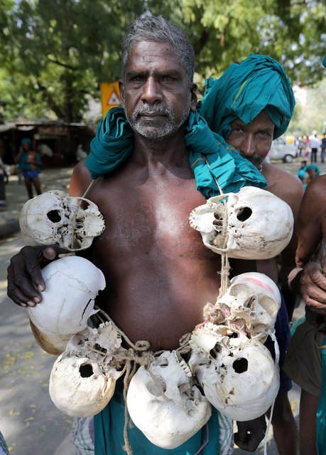 An Indian farmer from South Indian Rivers Interlinking Farmers Association holds human skulls claiming they belong to farmers who died in the past in Tamilnadu during a protest and hunger strike in New Delhi, India, 15 March 2017. (Photo by Harish Tyagi/EPA)