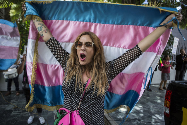 Lola Vazquez, who identifies as transgender, waves a transgender flag during a protest against a deal Guatemalan President Jimmy Morales' government signed with Washington that would force Salvadoran and Honduran migrants to request asylum in Guatemala instead of the United States, in Guatemala City, Wednesday, July 31, 2019. Critics of the deal point out that Guatemala has the same problems that are driving Hondurans and Salvadorans to flee their homes: violence, poverty, joblessness and a prolonged drought that has severely hurt farmers. (Photo by Oliver de Ros/AP Photo)