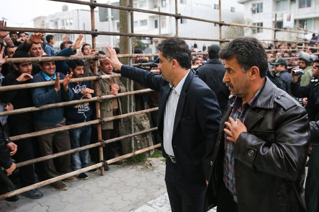 Bystanders applaud Abdolghani Hosseinzadeh (R) the father of Abdolah, an Iranian youth killed by fellow national Balal in a street fight with a knife in 2007, after he and his wife pardoned their son's convicted murderer, during his execution ceremony in the northern city of Nowshahr on April 15, 2014. The mother of Hosseinzadeh spared the life of Balal, with an emotional slap in the face as he awaited execution prior to removing the noose around his neck. (Photo by Araash Khamooshi/AFP Photo/ISNA)