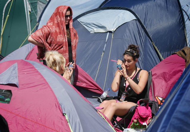 A festival goer puts on her make up amongst the tents during Glastonbury Music Festival on Saturday, June 27, 2015 at Worthy Farm, Glastonbury, England. (Photo by Joel Ryan/Invision/AP Photo)