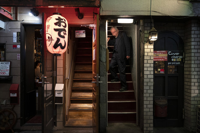 A man walks down the steps of a bar at the Golden Gai in the Shinjuku district of Tokyo, July 17, 2019. (Photo by Jae C. Hong/AP Photo)