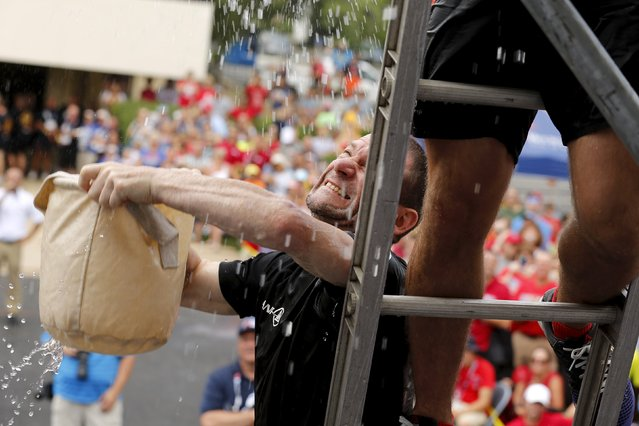 Will Schepens of a Belgian team from Brussels passes 30-pound (13.6 kg) bags of water up the ladder in the bucket brigade competition of the Firefighter Muster event at the World Fire and Police Games in Fairfax, Virginia July 4, 2015. (Photo by Jonathan Ernst/Reuters)