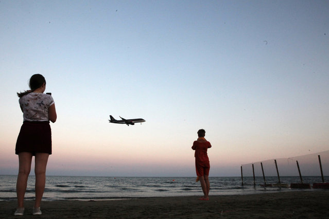 Tourists take pictures on a beach while an airplane prepares to land at Larnaca International Airport, Cyprus October 22, 2017. (Photo by Yiannis Kourtoglou/Reuters)