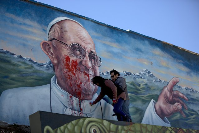 City workers clean a painting of Pope Francis defaced with red paint in El Alto, Bolivia, Tuesday, July 7, 2015. The pope will arrive to Bolivia on Wednesday during his South American tour. (Photo by Rodrigo Abd/AP Photo)