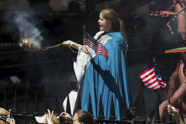 A clergy member spreads incense as she stands outside Trinity Church as the U.S. women's soccer team passes in floats during the ticker tape parade up Broadway in lower Manhattan to celebrate their World Cup final win over Japan in New York, July 10, 2015. (Photo by Mike Segar/Reuters)