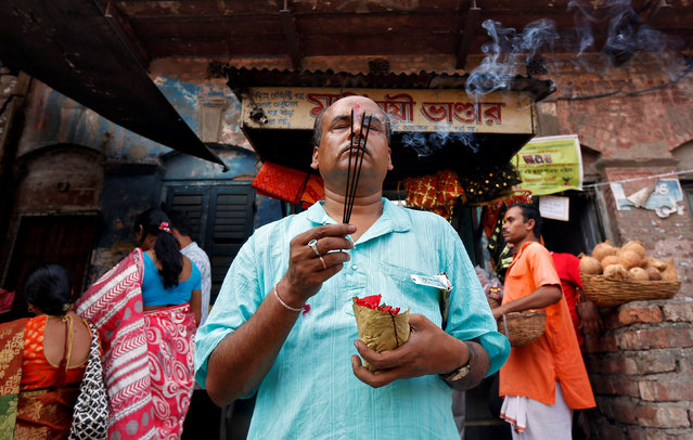 A Hindu devotee offers prayers inside a temple on the first day of the Bengali New Year in Kolkata, April 15, 2017. (Photo by Rupak De Chowdhuri/Reuters)
