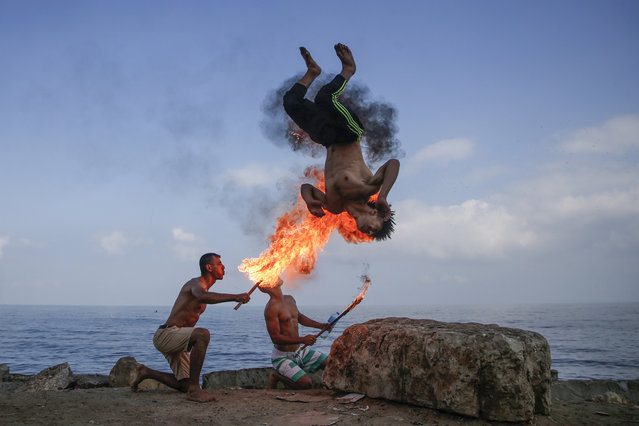 Palestinian men perform fire breathing on the beach as an entertainment for children during the summer vacation in Gaza City on August 1, 2019. (Photo by Mohammed Abed/AFP Photo)