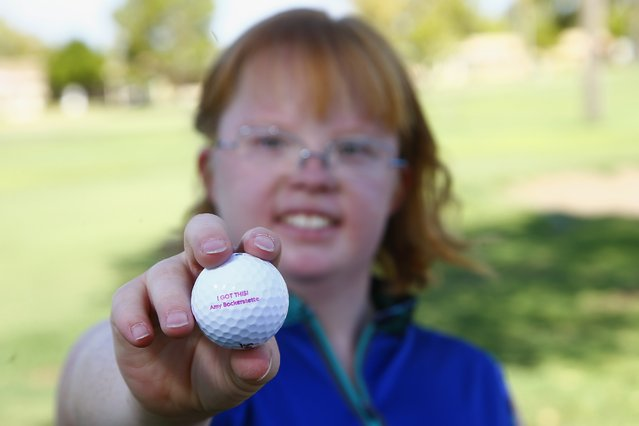 In this August 28, 2019, photo, Amy Bockerstette, the golfer with Down syndrome who was an internet sensation by making par at the 16th hole at the Phoenix Open with soon-to-be 2019 U.S. Open champion Gary Woodland, smiles as she holds up a personalized logo golf ball after her golf lesson at Palmbrook Country Club in Sun City, Ariz. (Photo by Ross D. Franklin/AP Photo)