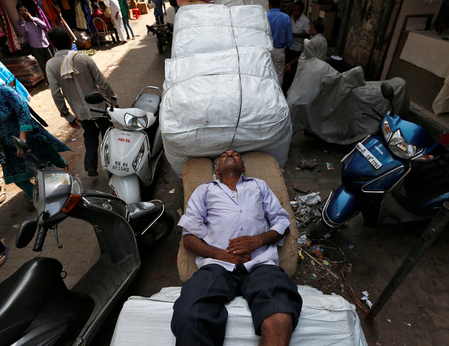 A labourer rests on a handcart on a hot summer day in Mumbai, India, May 23, 2016. (Photo by Danish Siddiqui/Reuters)