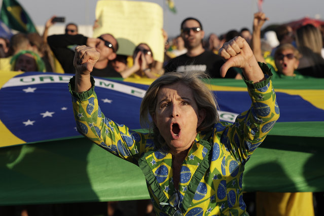 A supporter of Brazil's President Jair Bolsonaro shouts slogans and flashes thumbs down during a protest against the decision taken by the Supreme Court facilitating the release from jail of former President Lula Inacio Lula da Silva, in front at the National Congress building in Brasilia, Brazil, Saturday, November 9, 2019. Da Silva addressed thousands of jubilant supporters outside a union headquarters on Saturday, a day after he was freed. (Photo by Eraldo Peres/AP Photo)
