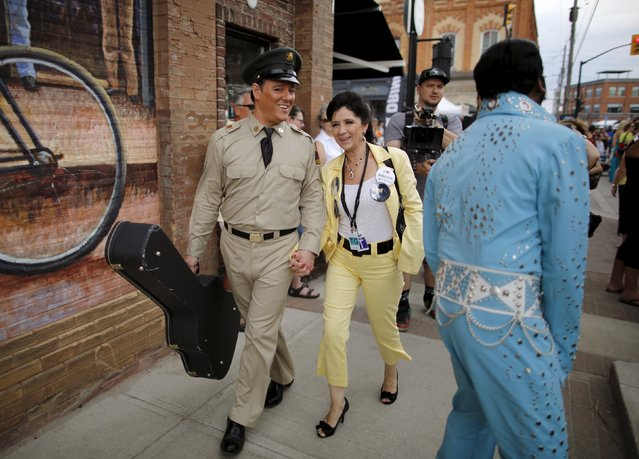 Elvis Presley tribute artist Bruce Stewart (L) of Georgian Bay, Ontario passes Lorenz Francke of Scarborough, Ontario during the four-day Collingwood Elvis Festival in Collingwood, Ontario July 25, 2015. (Photo by Chris Helgren/Reuters)