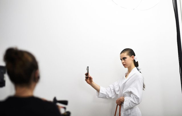 A model takes a selfie during hair and make-up inside Blenheim Palace ahead of a fashion show presenting the Dior, Cruise 2017 Collection, in Woodstock, Britain May 31, 2016. (Photo by Dylan Martinez/Reuters)