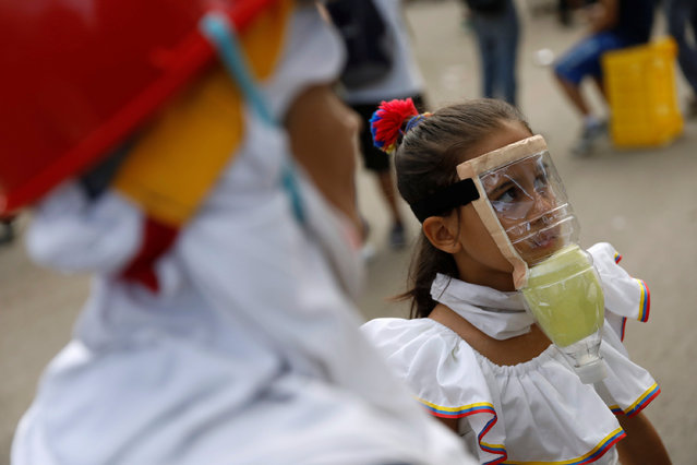A girls wears a homemade gas mask during a rally against President Nicolas Maduro in Caracas, Venezuela, May 27, 2017. (Photo by Carlos Garcia Rawlins/Reuters)