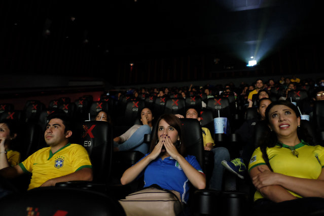 Soccer fans react during the 2014 World Cup opening match in a movie theatre in Guatemala City June 12, 2014. (Photo by Jorge Dan Lopez/Reuters)