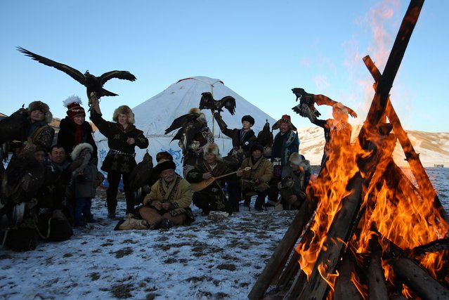 Hunters with their tamed golden eagles and hawks gather around a bonfire during a traditional hunting contest outside the village of Kaynar in Almaty region, Kazakhstan on December 8, 2019. (Photo by Pavel Mikheyev/Reuters)