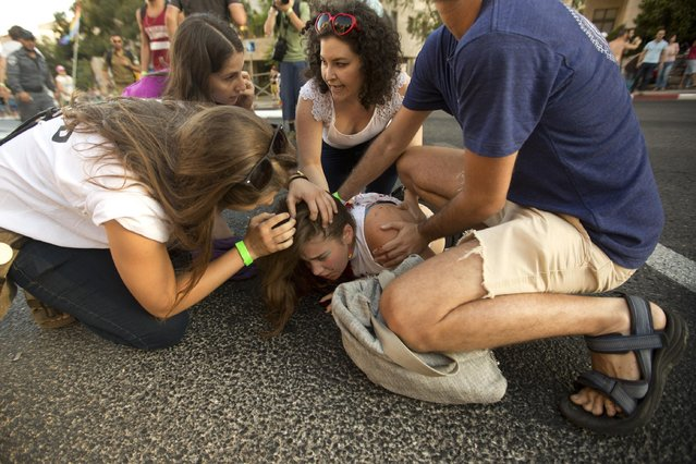 People help a wounded person after Yishai Schlissel, an ultra-Orthodox Jew, attacked people with a knife during a gay pride parade in Jerusalem on Thursday, July 30, 2015. Schlissel lunged into a group of revelers leading Jerusalem's annual gay pride parade and stabbed several of them Thursday evening as they marched in the holy city, Israeli police and witnesses said. (Photo by Sebastian Scheiner/AP Photo)