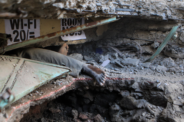A view of the leg of a man trapped inside a collapsed six-storey building in Nairobi, Kenya, 06 December 2019. Local media reported that s​everal people are feared trapped as the rescue operation continues. (Photo by Daniel Irungu/EPA/EFE)