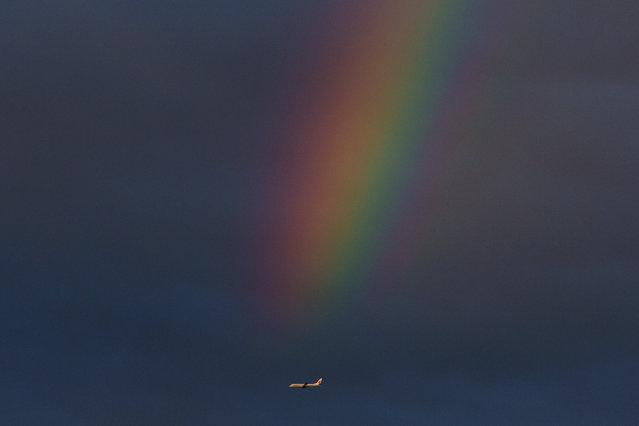 An Air China jet flies past a rainbow over Beijing Friday, June 6, 2014. (Photo by Alexander F. Yuan/AP Photo)