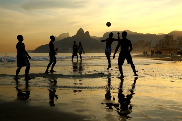 Young men play beach football as the sunsets on Ipanema beach on June 25, 2014 in Rio de Janeiro, Brazil. (Photo by Richard Heathcote/Getty Images)