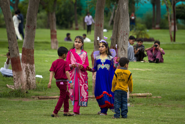 Pakistani children in new clothes visit a park to celebrate the Eid al-Fitr holidays in Rawalpindi, Pakistan, Saturday, July 18, 2015. (Photo by Anjum Naveed/AP Photo)