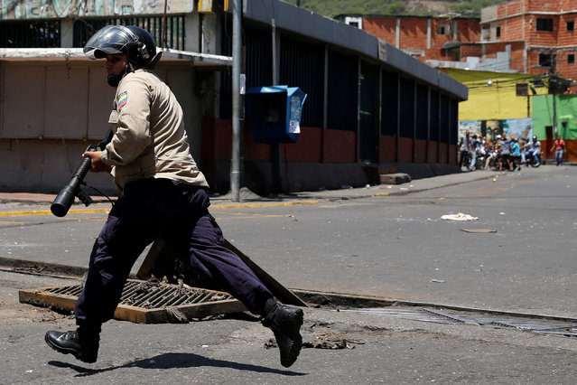 A riot policeman runs during clashes with Venezuelan protesters during a demonstration over food shortage and against Venezuelan President Nicolas Maduro's government in Caracas, Venezuela, June 10, 2016. (Photo by Carlos Garcia Rawlins/Reuters)