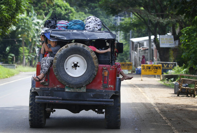 Residents fleeing the besieged city of Marawi travel to an evacuation center, Friday, May 26, 2017, in Bal-oi township, southern Philippines. Philippine army generals say dozens of Islamic State group-linked extremists have been killed in two days of fighting in a southern city that has been under siege since one of Asia's most-wanted militants evaded capture and dozens of rebels came to his aid. (Photo by Bullit Marquez/AP Photo)