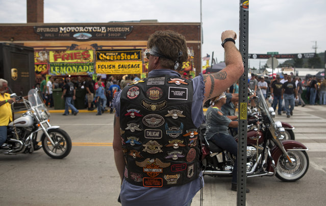 Mike Shannon, of Bloomington, Minnesota, watches the traffic roll through downtown while participating in the annual Sturgis Motorcycle Rally in Sturgis, South Dakota, August 4, 2015. (Photo by Kristina Barker/Reuters)