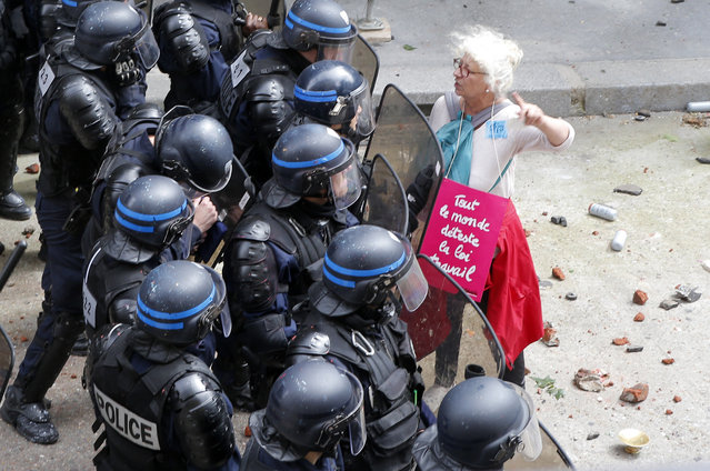 "A woman, with a poster reading ""We all hate the Labor Law"", argues with riot police officers during a demonstration in Paris Tuesday, June 14, 2016. Protesters in Paris threw projectiles at police officers, who responded with tear gas, amid demonstrations by tens of thousands of people opposed to a proposed labor law. (Photo by Francois Mori/AP Photo)"