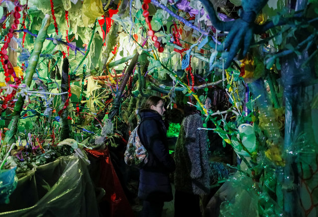 "People attend an exhibition ""Wrapped in plastic"" in Kiev, Ukraine on November 26, 2019. Ukrainian director Vladi Yudi used plastic in various shapes and forms to create settings for a horror cartoon titled ""Wrapped in plastic"", with main character Garbie, combination of Barbie and garbage. Cartoon decorations were embedded into a bigger same-name exhibition fully made of recyclable and non-recyclable waste. (Photo by Gleb Garanich/Reuters)"