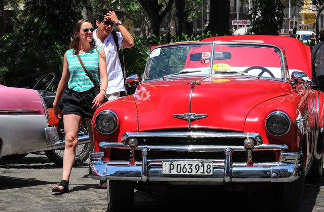 Tourists from the United States look at an old car in Havana, on April 6, 2015. (Photo by Yamil Lage/AFP Photo)