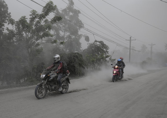 Motorcycles ride along an ash covered road as they evacuate to safer grounds as Taal volcano in Lemery, Batangas, southern Philippines on Monday, January 13, 2020. (Photo by Aaron Favila/AP Photo)