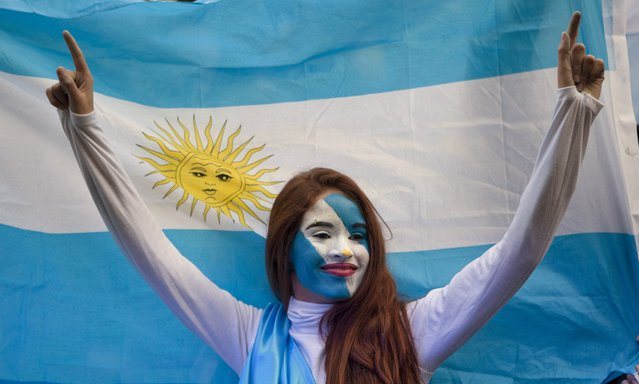 An Argentina soccer fan poses in front of an Argentine flag before a World Cup semifinal match between Argentina against Netherlands, on a street where an outdoor screen has been set for viewing, in Buenos Aires, Argentina, Wednesday, July 9, 2014. (pHOTO BY Eduardo Di Baia/AP Photo)