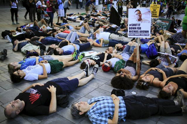 """Protesters perform a """"die-in"""" while they take part in a rally at Barclays Center marking the first anniversary of the death of Michael Brown, in Brooklyn, New York August 9, 2015. (Photo by Eduardo Munoz/Reuters)"""
