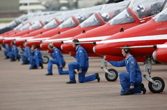 Ground staff kneel in front of The Royal Air Force aerobatic team, the Red Arrows, during The Royal International Air Tattoo at the RAF in Fairford July 11, 2014. (Photo by Stefan Wermuth/Reuters)