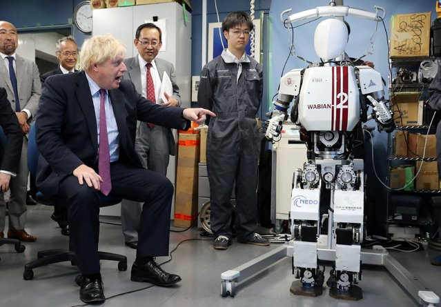 Britain's Foreign Secretary Boris Johnson (L) looks at the bipedal humanoid robot Wabian2 at the Research Institute for Science and Engineering at Waseda University's Kikuicho campus in Tokyo on July 20, 2017. Johnson is on a three-day visit to Japan. (Photo by Eugene Hoshiko/AFP Photo)