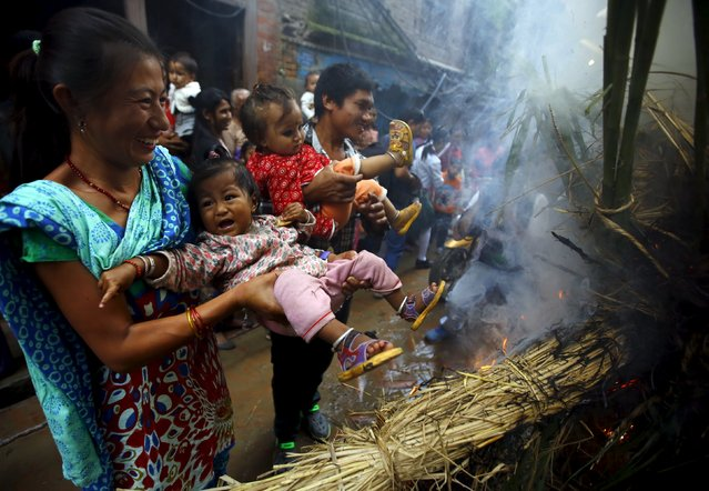 A woman swings a child around the fire, where an effigy of the demon Ghantakarna was burnt to symbolize the destruction of evil, during the Ghantakarna festival at the ancient city of Bhaktapur, Nepal August 12, 2015. (Photo by Navesh Chitrakar/Reuters)