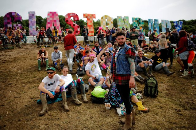 Revellers gather around the Glastonbury Festival sign at Worthy Farm in Somerset, Britain, June 23, 2016. (Photo by Stoyan Nenov/Reuters)