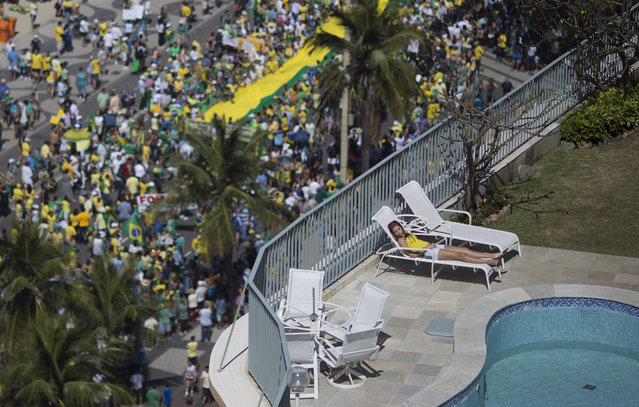 A woman sleeps in a residential penthouse while thousands below march in an anti-government protest demanding the impeachment of Brazil's President Dilma Rousseff, in at Copacabana beach, Rio de Janeiro, Brazil, Sunday, August 16, 2015. Demonstrators are taking to the streets across Brazil for a day of nationwide anti-government protests. President Rousseff's second term in office has been shaken by a snowballing corruption scandal involving politicians from her Workers  Party. (Photo by Leo Correa/AP Photo)