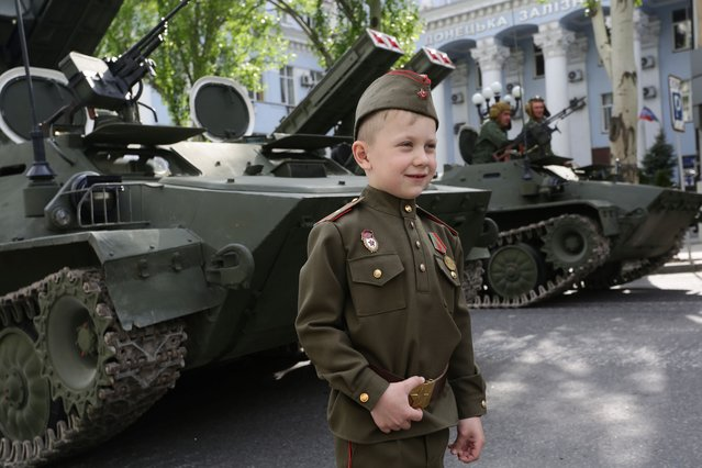 This photo taken on May 5, 2016 shows a boy wearing a Soviet-era uniform standing in front of an APC during rehearsal of Victory Day parade in Donetsk. Youth movements are only one example among many of this infatuation with the Soviet past. A least a dozen of them are now listed in the self-proclaimed People's Republic of Donetsk. During the May 9 parade celebrating the victory over Nazi Germany in 1945, many parents had covered their children's heads in red caps, typical of Soviet pioneers. (Photo by Aleksey Filippov/AFP Photo)
