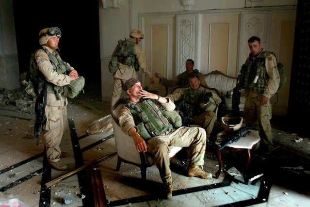U.S. Army Stf. Sgt. Chad Touchett (center) relaxes with comrades from A Company, 3rd Battalion, 7th Infantry Regiment,  following a search in one of Saddam Hussein's palaces damaged after a bombing, in Baghdad