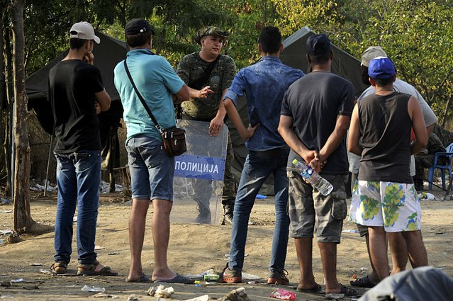 A Macedonian police officer talks with migrants standing on the Greek side at the Greek-Macedonian border, August 20, 2015. (Photo by Alexandros Avramidis/Reuters)