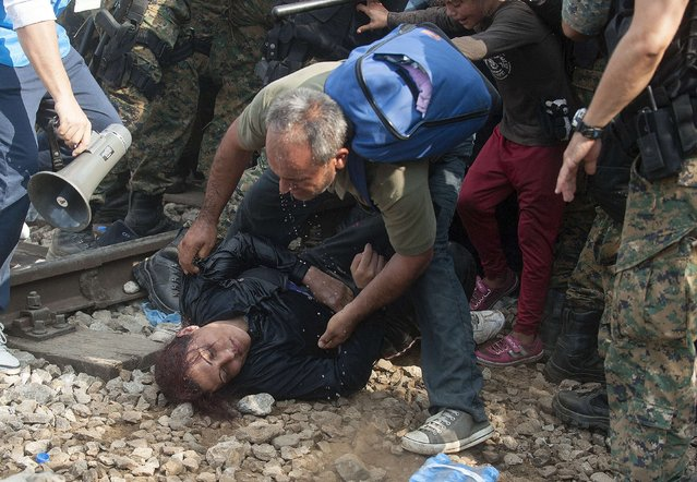 """A man assists a fallen woman as police block a group of migrants trying to cross the Macedonian-Greek border near the town of Gevgelija on August 21, 2015. Macedonia said on August 20 that it had declared a """"state of emergency"""" on its southern border with Greece and would draft in the army to help control the influx of migrants crossing the frontier. (Photo by Robert Atanasovski/AFP Photo)"""