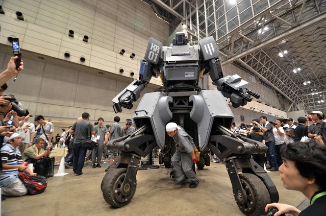 """Engineer Mitsugoro Kurata (C) walks in front of Japanese electronics company Suidobashi Heavy Industry's newly unveiled robot """"Kuratas"""" at the Wonder Festival in Chiba, suburban Tokyo on July 29, 2012. The Kuratas robot, which will go on sale with a price tag of one million USD, measures four meters in height, weighs four tons and has four wheeled legs that can either be controlled remotely through the 3G network or by a human seated within the cockpit.   (Photo by Yoshikazu Tsuno/AFP Photo)"""