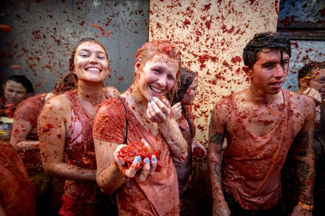 """Revellers throw tomato pulp at each other during the annual """"Tomatina"""" festivities in the village of Bunol, near Valencia on August 26, 2015. (Photo by Biel Alino/AFP Photo)"""